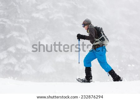 Young Man Snowshoeing in Heavy Snow  - stock photo