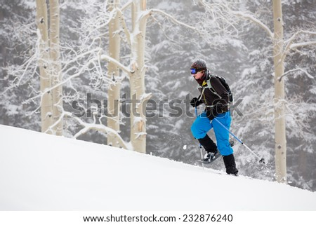 Young Man Snowshoeing in Wintry Forest - stock photo