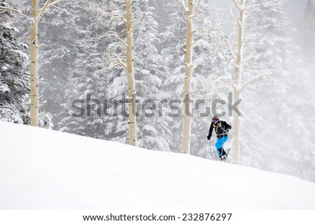 Young Man Snowshoeing Up Hill in Wintry Storm