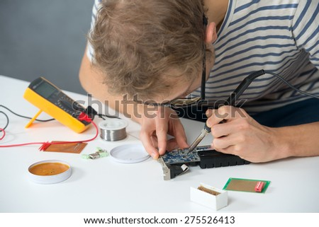Young man soldering home work on the table