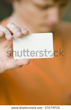 Young man somewhat in bad mood shows his blank card