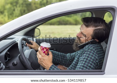 Young man speaking on phone and drinking coffee while driving his car