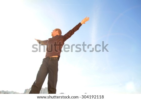 Young man spreading hands. Deep breathing carefree business man in the blue sky, happy european man. Happy business man open arms at the roof of a skyscraper. Life style concept. Blurred light. - stock photo