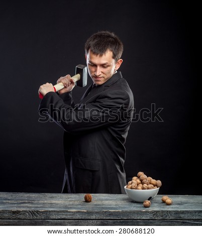 young man stabs a nut - stock photo