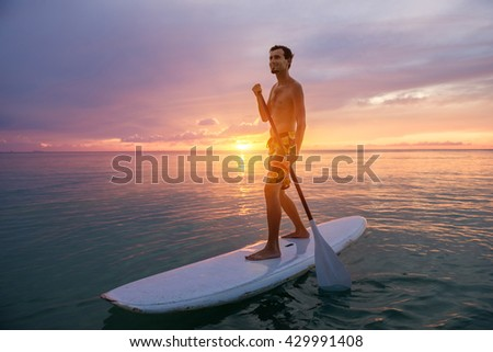 Young man stand up on paddle board and paddling out in tropical waters. Water sport near the beach on sunset - stock photo