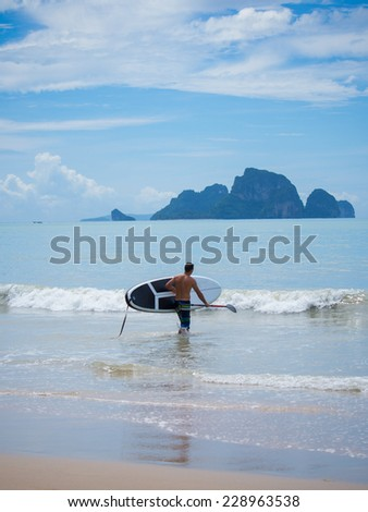 Young man stand up paddle boarding - stock photo