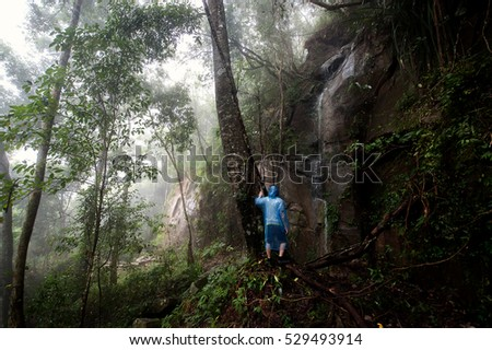 Young Man standing alone in forest outdoor with nature on background Travel Lifestyle and survival concept