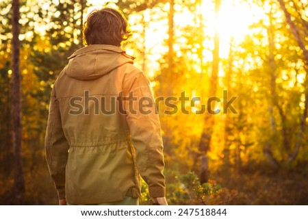 Young Man standing alone in forest outdoor with sunset nature on background Travel Lifestyle and survival concept  - stock photo