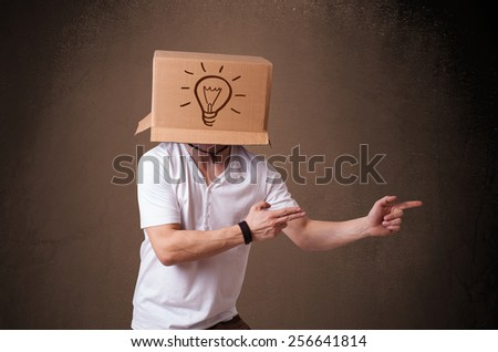 Young man standing and gesturing with a cardboard box on his head with light bulb - stock photo