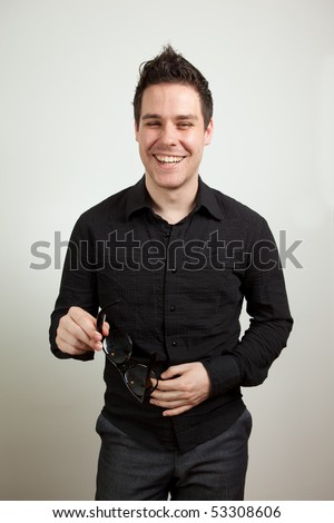 Young man standing and laughing - stock photo