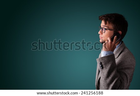 Young man standing and making phone call with copy space - stock photo