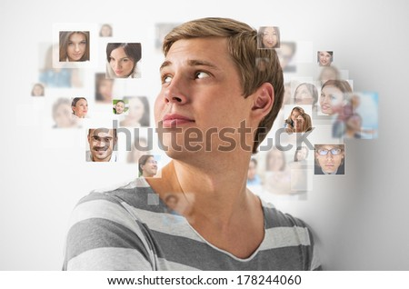 Young man standing and smiling with many different people's faces around him. Technology social media network of friends and communication. - stock photo