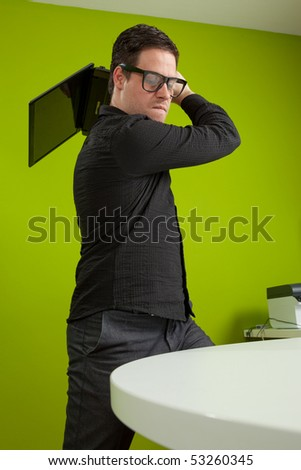 Young man standing and trying to smash his laptop - stock photo