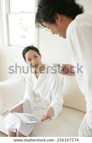 Young man standing beside a young woman and reading a magazine
