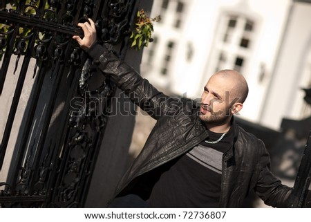 Young man standing by a gate - stock photo