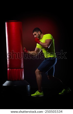 young man standing exercising with boxing bag in studio - stock photo