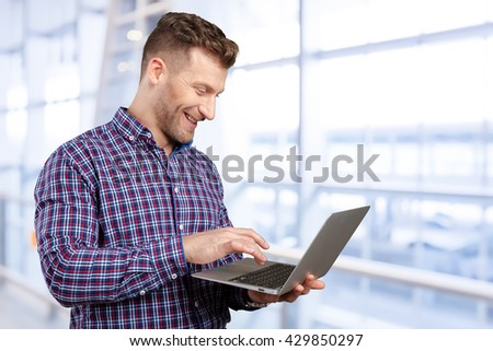 Young man standing, holding laptop computer, working.