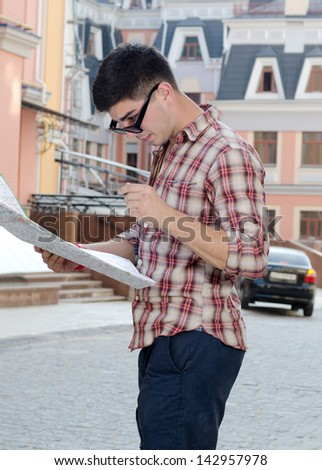 Young man standing in a town street with his sunglasses pushed down on his nose peering over the top at a tourist map - stock photo