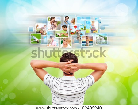 Young man standing in front of virtual preview of different images and choosing channel - stock photo
