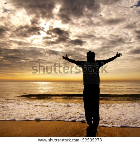 young man standing in the beach - stock photo