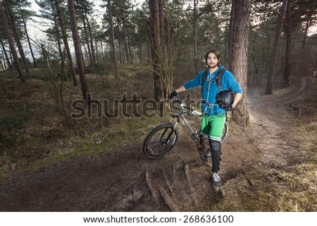 Young man standing in the forest posing proudly with his ATB bike - stock photo