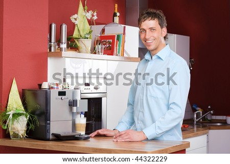 Young man standing in the kitchen beside a coffee machine - stock photo