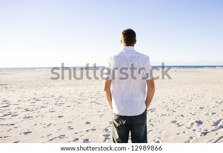 young man standing looking at the beach - stock photo