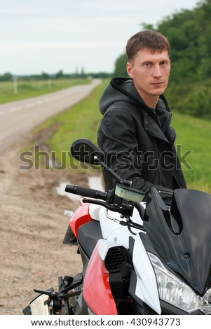 Young man standing near a motorcycle on an open road.