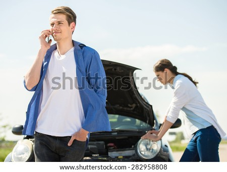 Young man standing near broken car and calling for help on phone. - stock photo