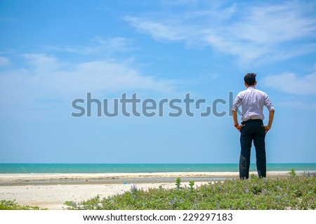 Young man standing near the beach and looking at sea