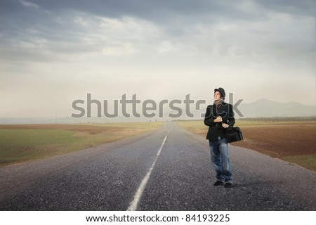 Young man standing on a countryside road - stock photo