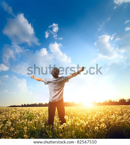 Young man standing on a meadow with raised hands and looking to a sky