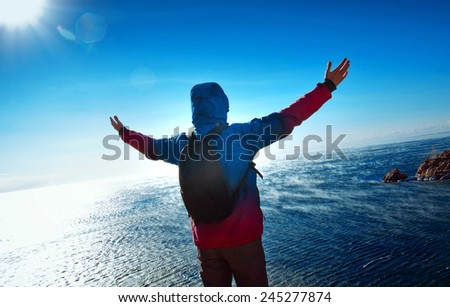 young man standing on a mountain with his arms raised - stock photo