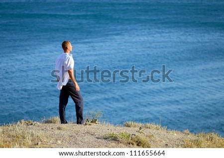 Young man standing on a rock and looking at sea - stock photo
