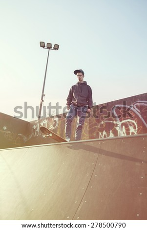 Young man standing on a skateboard preparing for a jump on a skate ramp - stock photo