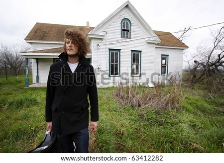 Young man standing on front of an abandoned house, holding a guitar case.