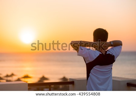 Young man standing on the balcony in carefree pose with hands behind his head, enjoying beautiful colorful sunrise or sunset sea landscape and fresh air, copy space, back view - stock photo