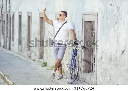Young man standing on the old town street with his bicycle beside him and taking a photo with his smart phone - stock photo