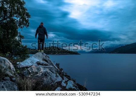 Young man standing on the stone near by fjord at night, Norway