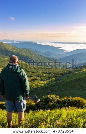Young man standing on the top of mountain and looking at beautiful mountain landscape in sunrise time, Carpathians