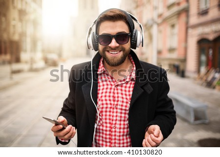 Young man standing on the town square and listening to the music - stock photo