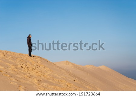 Young man standing on top of a dune