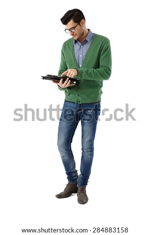 Young man standing over white background, holding and using tablet pc. Full-length. - stock photo