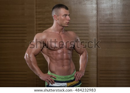 Young Man Standing Strong And Flexing Muscles - Muscular Athletic Bodybuilder Fitness Model Posing After Exercises