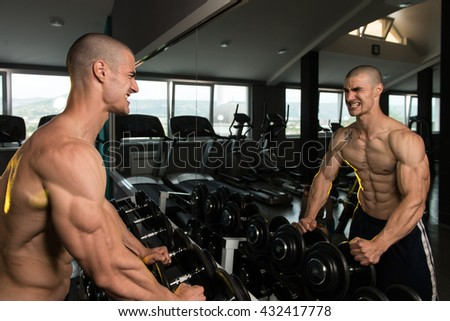 Young Man Standing Strong In Front Of A Mirror And Flexing Muscles - Muscular Athletic Bodybuilder Fitness Model Posing After Exercises - stock photo