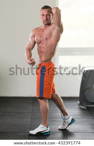 Young Man Standing Strong In The Gym And Flexing Muscles - Muscular Athletic Bodybuilder Fitness Model Posing After Exercises - stock photo
