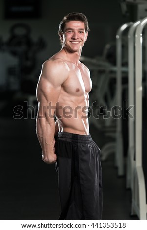 Young Man Standing Strong In The Gym And Flexing Side Triceps Pose - Muscular Athletic Bodybuilder Fitness Model Posing Exercises - stock photo