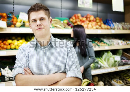Young man standing the front of shopping shelves - stock photo