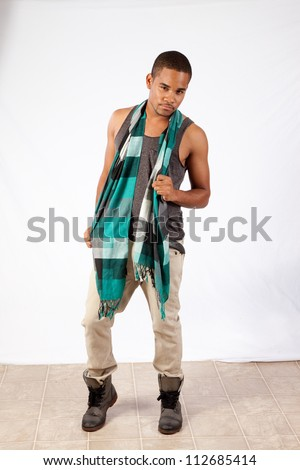 Young man standing with a scarf and a thoughtful, pensive expression - stock photo