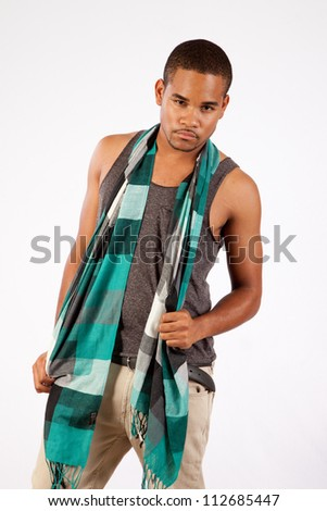 Young man standing with a scarf and a thoughtful, pensive expression